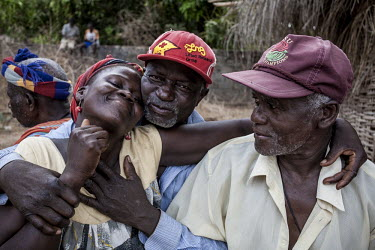Africa, Guinea-Bissau, Cacheu. 2013-03-23. A man with a red cap embraces his wife. Afrika.../Ernst Schade