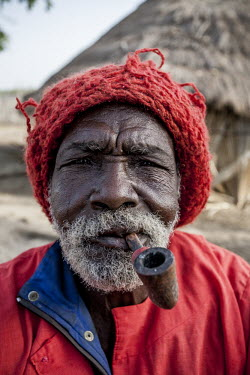 Africa, Guinea-Bissau, Djobel. 2013-03-26. The traditional leader of the village smokes his pipe.../Ernst Schade