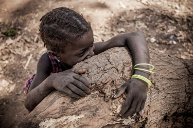 Africa, Guinea-Bissau, Cobiana. 2013-03-21. A shy young girl looks on visitors from behind a tree.../Ernst Schade
