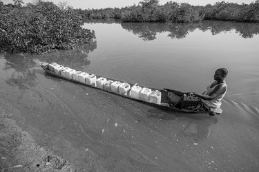 West-Africa, Guinea-Bissau, Djobel village. 2013-03-26. A woman rows her fully loaded canoe with.../Ernst Schade