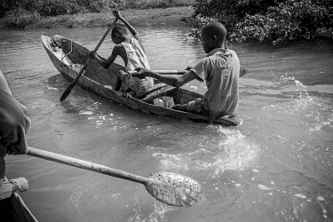 Africa, Guinea-Bissau, Bolol. 2013-04-04. Two boys row their canoe on the waterways near Bolol.../Ernst Schade