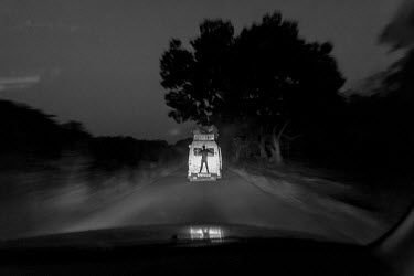 Africa, Guinea-Bissau, near Ingore. 2013-03-24. A guard hangs on the back of a small passengers bus.../Ernst Schade