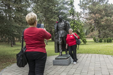 Two ladies making a picture with statue of Tito/Daphne Channa Horn