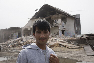 Refugee in front of former home/Daphne Channa Horn