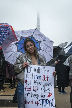 A young woman holds a sign with the lyrics of the rapper 2pac's Keep Ya Head Up song for women's.../Rose Lecat / Hans Lucas