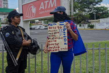 Central America - Nicaragua, capital city Managua: An anti-Ortega rebel holds a flyer with the.../Juan Carlos