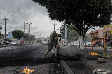 Central America - Honduras, capital city Tegucigalpa: A member of the military police cleans an.../Juan Carlos