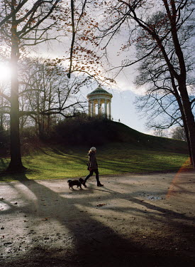 Girl and dog walking past the Monopteros in the English garden/Marleen Daniels
