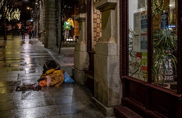 Portugal, Porto. 2020-12-28. A woman sits huddles on the pavement with her child half covered.../Ernst Schade