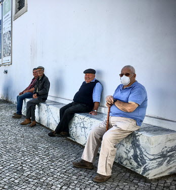 Portugal, Alentejo, Alcacovas. 2020-10-11. Men rest on a bench and are rather relaxed about the.../Ernst Schade