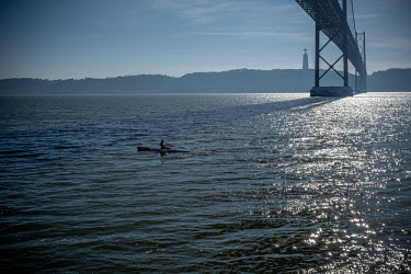 Portugal, Lisbon. 2021-01-17. A solo rower on an empty River Tagus passes under the suspension.../Ernst Schade