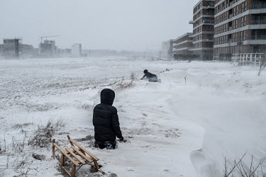 the Netherlands, Amsterdam, 08-02-2021 ;Snowstorm in Amsterdam, playing kids with a sledge Photo:.../Peter Boer