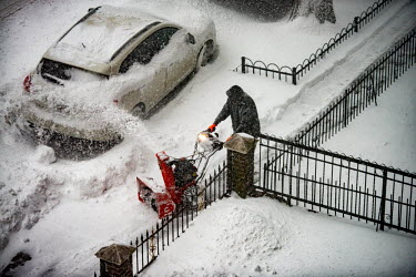 a man clears the side walks of Ocean Avenue during a snowstorm with a snow blower, the snow he.../Deen van Meer